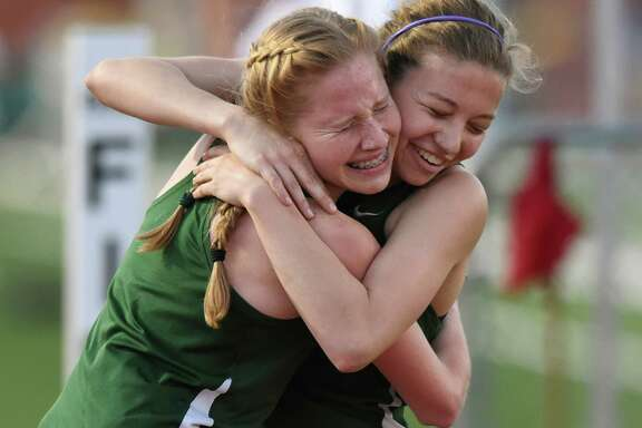 Alison Hepp, right, winner of the women's 1600 meter run, is embraced by Reagan teammate Anna King during the high school District 26-6A track and field championships at Heroes Stadium on Thursday, April 14, 2016.