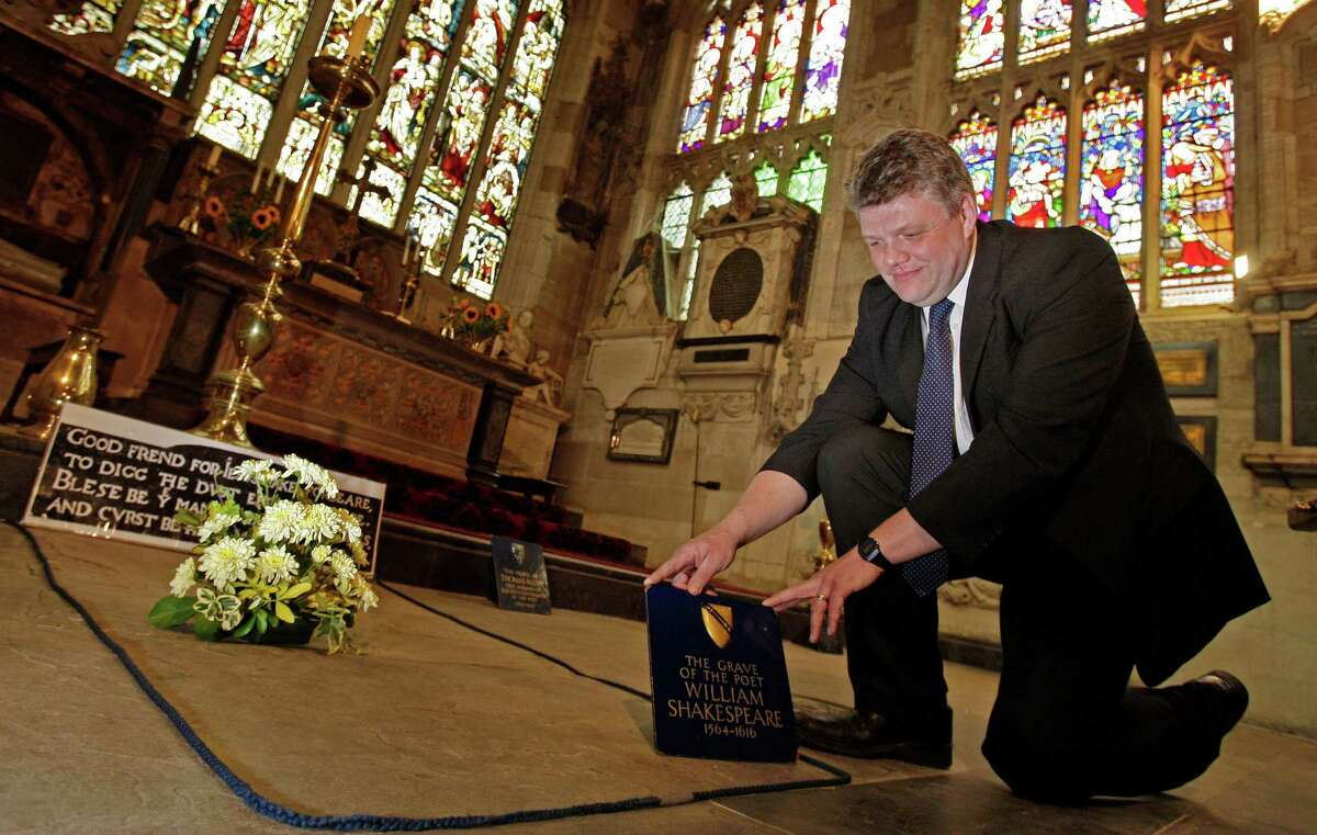 FILE - In this Monday, Sept. 21, 2009 file photo, Head Verger Jon Ormrod tends to the grave of William Shakespeare in the Chancel of Holy Trinity Church in Stratford Upon Avon, England. Archeologists who scanned the grave of William Shakespeare say they have made a startling discovery: His skull appears to be missing. The researchers used ground-penetrating radar to explore beneath the playwright's tomb in Stratford-upon-Avon's Holy Trinity Church. Kevin Colls, who led the study, said the team found