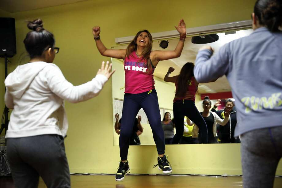 Marcela Caetano, who left one daughter in Mexico and gave birth to another in the U.S., teaches a Zumba class in Richmond. Photo: Scott Strazzante, The Chronicle