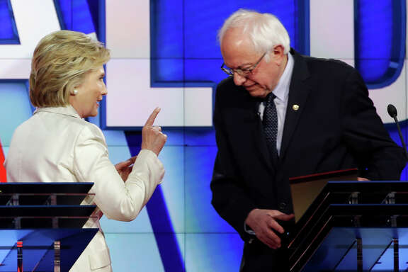 Democratic presidential candidate Hillary Clinton, left, gestures towards Democratic presidential candidate Sen. Bernie Sanders, I-Vt., at the start of a break during the CNN Democratic Presidential Primary Debate at the Brooklyn Navy Yard on Thursday, April 14, 2016 in New York.