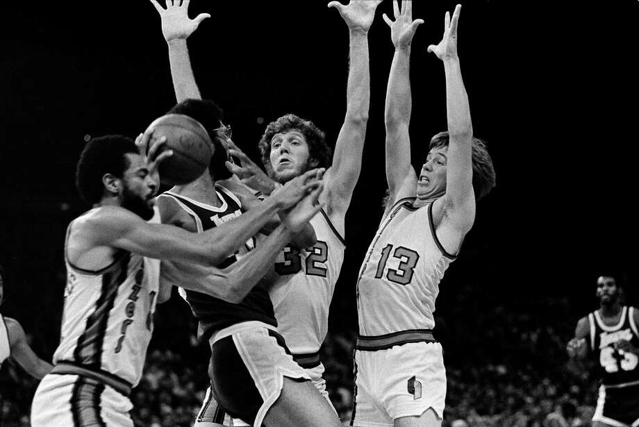 Los Angeles Lakers Kareem Abdul-Jabbar is surrounded by three Portland Trail Blazers during game action in Portland, Ore., April 9, 1977. From left: Lionel Hollins, Abdul-Jabbar, Bill Walton and Dave Twardzik. (AP Photo/Jack Smith) Photo: Jack Smith / AP / AP