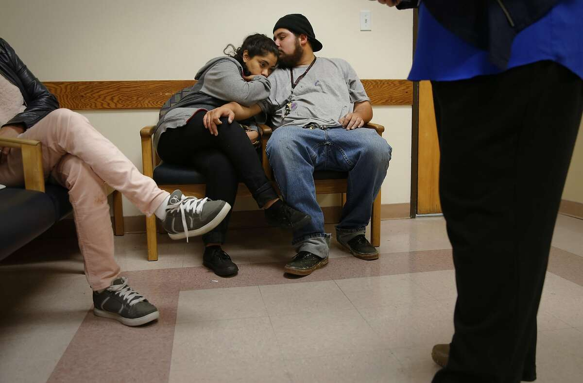 Paula Sanchez, of Richmond waits to see a physician along with her boyfriend Hector Nunez, San Pablo at the LifeLong Medical Care an urgent care clinic in San Pablo, California on Thurs. April 14, 2016, is operating across the street from the Doctors Medical Center hospital which closed down a year ago. Sanchez is on her third visit to the clinic.