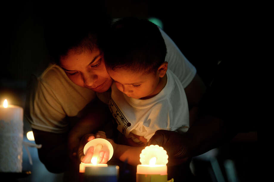 Sabrina Sanchez helps Riccardo, 2, light his candle during the 26th annual Crime Victims' Candlelight Vigil at the Jefferson County Courthouse on Thursday evening. The Sanchez family was there remembering Fernando Sanchez, who died from a drunk driving wreck in December 2015. Photo taken Thursday 4/14/16 Ryan Pelham/The Enterprise Photo: Ryan Pelham / ©2016 The Beaumont Enterprise/Ryan Pelham