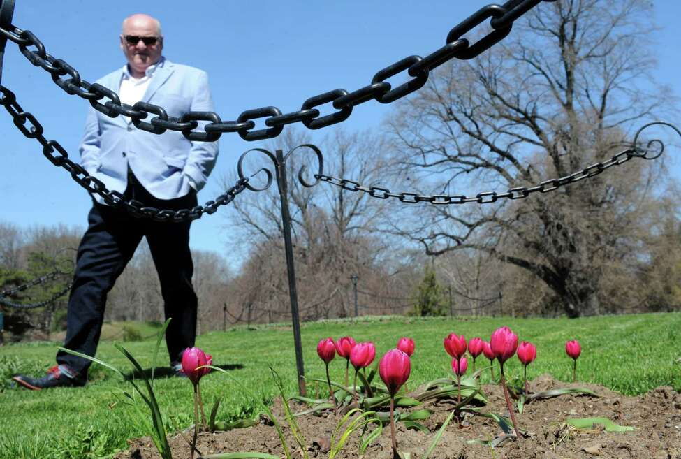 Brian Rider of Albany checks out some early blooming tulips in Washington Park on Friday, April 15, 2016, in Albany , N.Y. (Michael P. Farrell/Times Union)