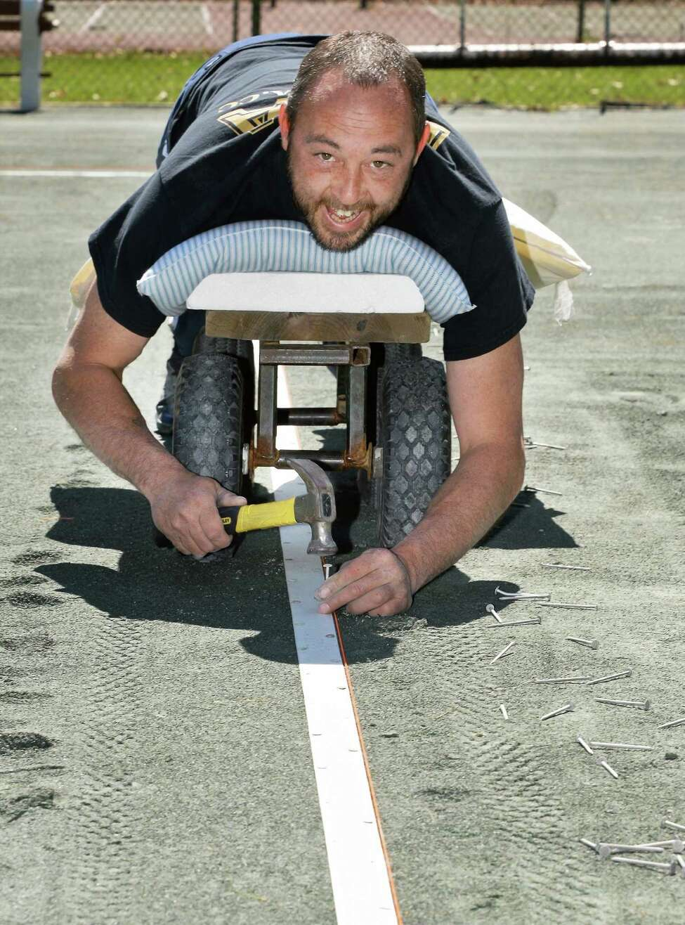 Volunteer Joseph Sweet installs tennis line tape at the Saratoga Spa State Park tennis courts Friday April 15, 2016 in Saratoga Springs, NY. (John Carl D'Annibale / Times Union)