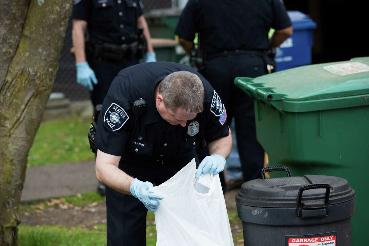 SPD officer Aaron Stoutz goes through trash cans on the 900 block of 20th Ave after more human remains were found on Friday, April 15, 2016. The remains are in close vicinity to where Ingrid Lyne's remains were found.