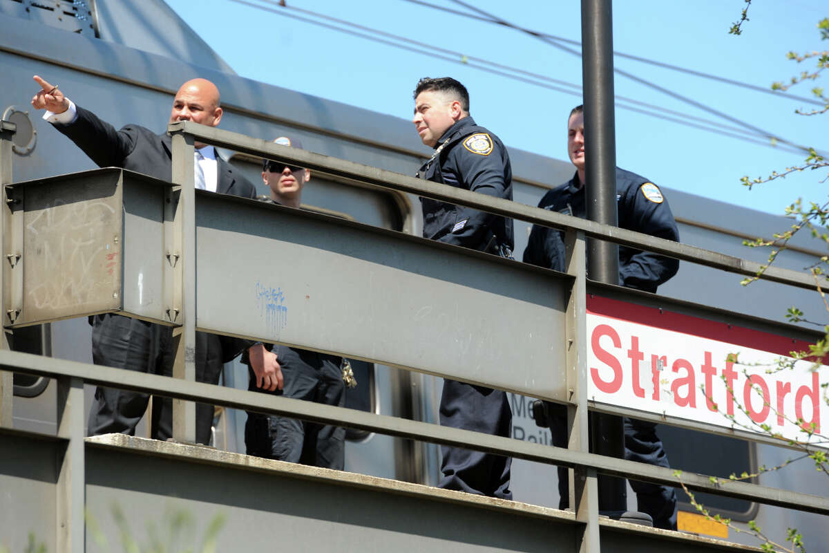Investigators look over the scene at the Stratford train station on Friday. A pedestrian was struck and killed by a Metro-North train near the station Friday a short time after noon.