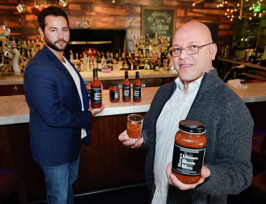 At right, Manny Ferreira, founder of Manny's Ultimate Bloody Mary, holding his product along with Tony Galazin, background, the chief operating officer of the company, at the bar in the J House Greenwich Hotel in the Riverside section of Greenwich. Photo: Bob Luckey Jr. / Hearst Connecticut Media / Greenwich Time