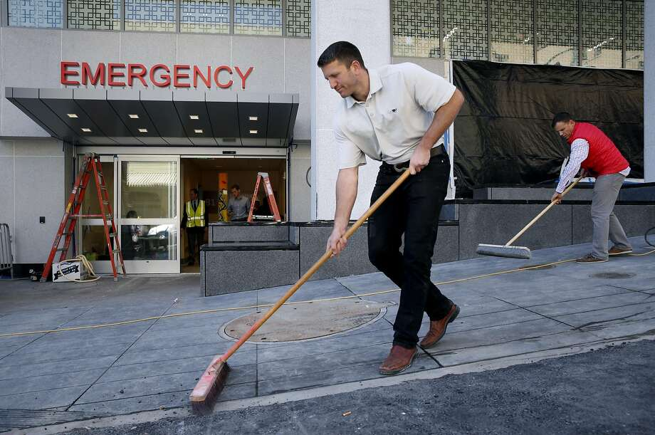 Sam Rabb and Aaron Peterson (right) sweep the sidewalk in front of the Emergency Room entrance of the new Chinese Hospital building in San Francisco, Calif. on Friday, April 15, 2016. The new tower replaces the original hospital building which opening in 1915 and will start receiving patients in June. Photo: Paul Chinn, The Chronicle
