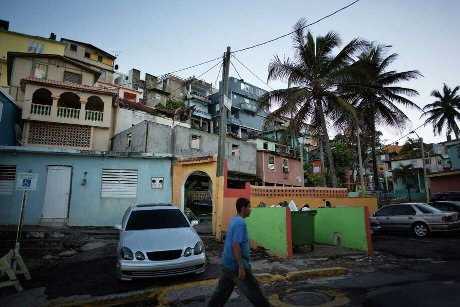Pedestrians walk through La Perla, an informal settlement in Old San Juan, Puerto Rico. Skeptical lawmakers at the House Natural Resources Committee heard testimony last week on a plan to rescue Puerto Rico from its giant debt defaults, as witnesses warned that only quick action by Congress could keep a bad situation from becoming a lost decade. Photo: VICTOR J. BLUE /NYT / NYTNS