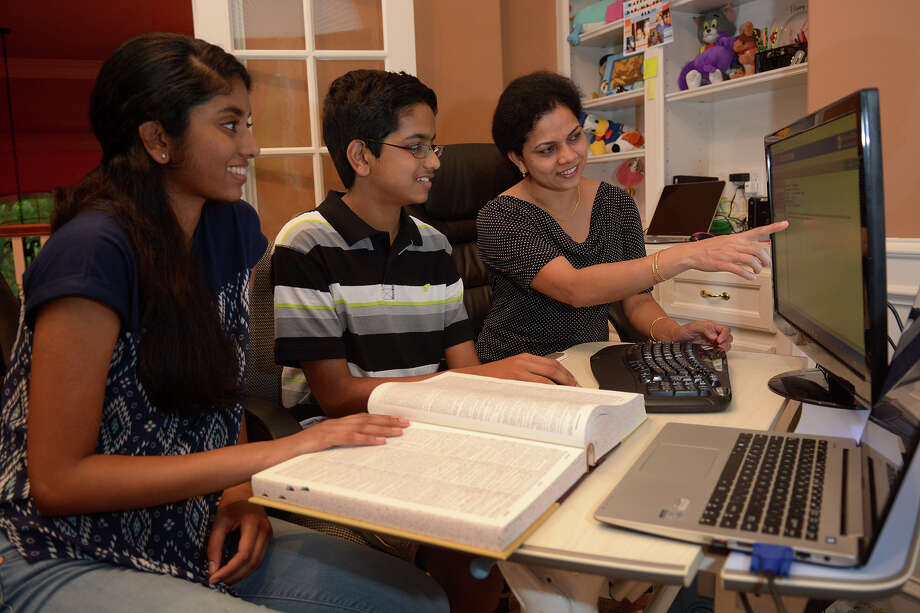 Shourav Dasari, 13, center, a 7th grader at McCullough Junior High and co-champion of the Houston Public Media Spelling Bee, gets some coaching from sister Shobha, 15, left, a freshman at The Woodlands College Park High School and former spelling bee champion, and their mom, Usha in advance of the national spelling bee competition. (Photo by Jerry Baker/Freelance) Photo: Jerry Baker, Freelance
