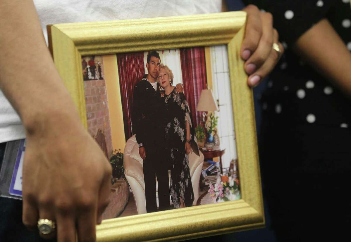 Allan Sabillon holds a photo of him and his mother after he returned from his second deployment during a news conference about the charges against Alexis De Larosa Sosa, who is suspected in the hit and run death of Sabillon's parents on Friday, April 15, 2016, in Houston.
