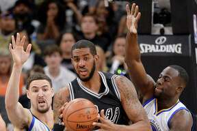 San Antonio Spurs forward LaMarcus Aldridge, center, tangles with Golden State Warriors' Klay Thompson, left, and Draymond Green during the first half of an NBA basketball game, Sunday, April 10, 2016, in San Antonio. Golden State won 92-86. (AP Photo/Darren Abate)