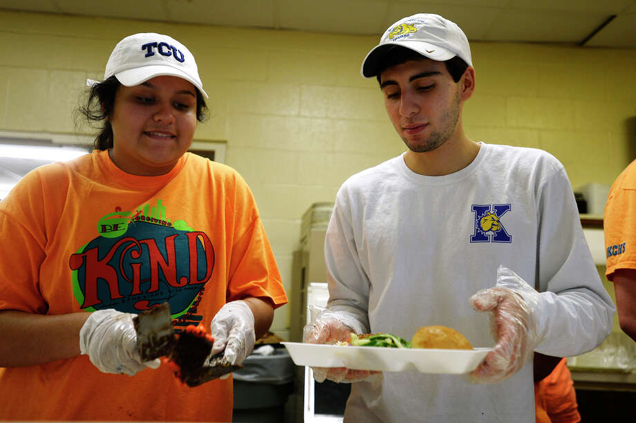 Katie Hernandez and Munir Pavez prepare meals at Some Other Place's soup kitchen during Monsignor Kelly Catholic High School's 5th annual Spring Into Action service day on Friday. The entire school, including teachers, staff and parent volunteers spend the day volunteering around the city.  Photo taken Friday 4/15/16 Ryan Pelham/The Enterprise Photo: Ryan Pelham / ©2016 The Beaumont Enterprise/Ryan Pelham