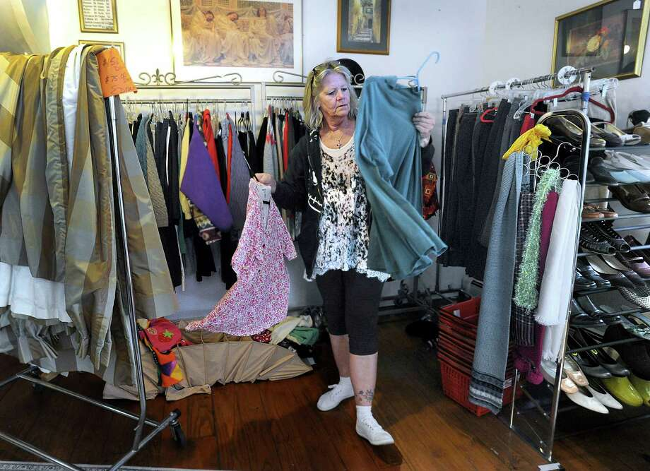 Deb Pennywell, of New Milford, a volunteer at Healing The Children Thrift, sorts through clothes Thursday, April 14, 2016. The thrift shop at 27 East Street in New Milford is closing Saturday. Photo: Carol Kaliff / Hearst Connecticut Media / The News-Times