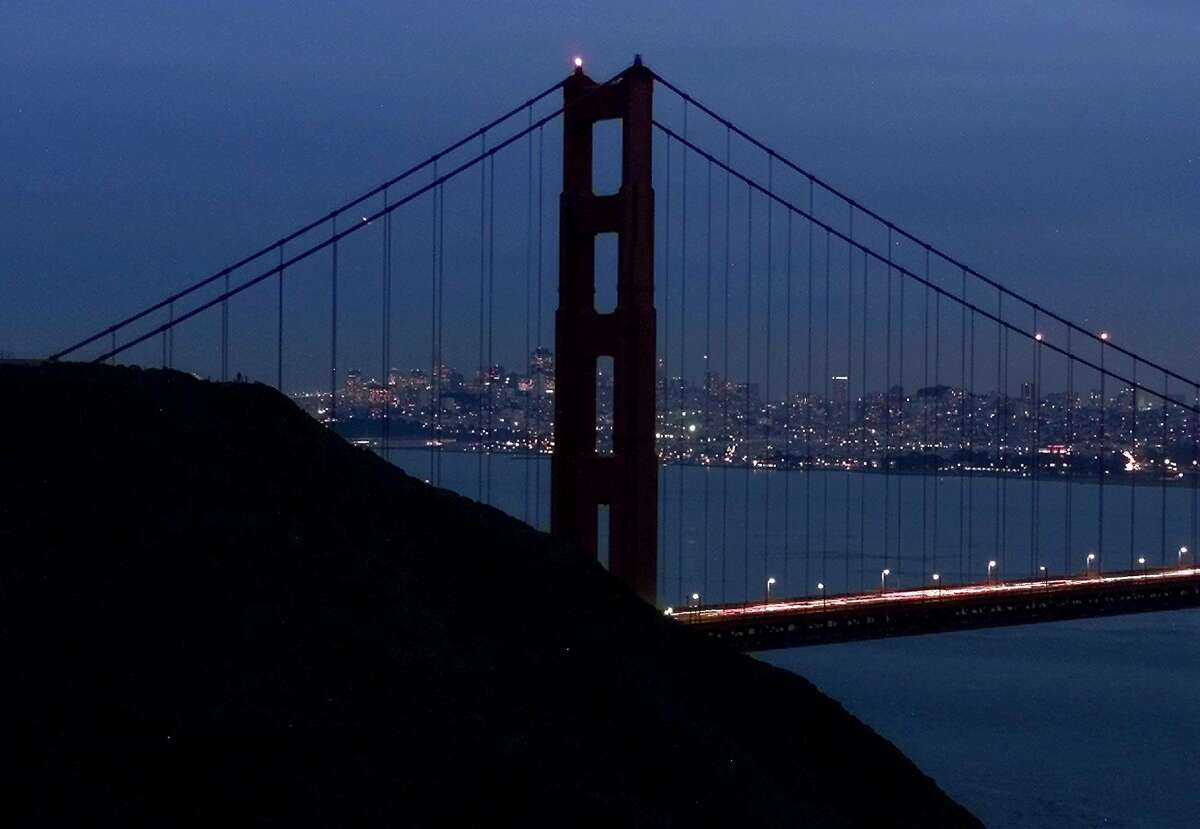The north tower of the Golden Gate Bridge, which is normally illuminated, remains darkened in Sausalito, Calif., Thursday, Jan. 18, 2001, as California continues its energy shortages. Earlier in the day rolling blackouts were experienced for the second straight day in Northern California. (AP Photo/Eric Risberg). HOUCHRON CAPTION (01/21/2001): The north tower of the Golden Gate Bridge, which is normally illuminated, was darkened Thursday as California experiences rolling blackouts due to the energy crisis. Concern is building among estern states that California's problems may spread.