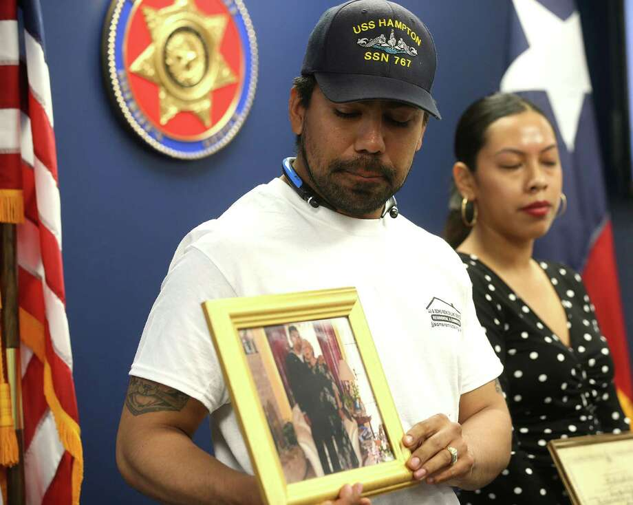 Allan Sabillon holds a photo of him and his mother, Maria Sabillon, who was killed in a street racing crash. Sabillon's wife, Dianne, is at right.  Photo: Elizabeth Conley, Staff / © 2016 Houston Chronicle