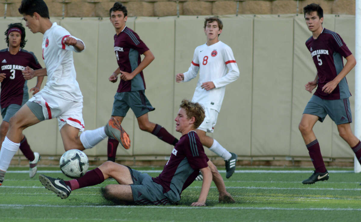 Cinco Ranch senior midfielder Brady Johnston, center, makes a play against a Coppell defender during the second half of their Boys Class 6A semifinal matchup at the UIL Soccer State Championships at Birkelbach Field in the Georgetown ISD Athletic Complex in Georgetown on Friday, April 15, 2016. (Photo by Jerry Baker/Freelance)