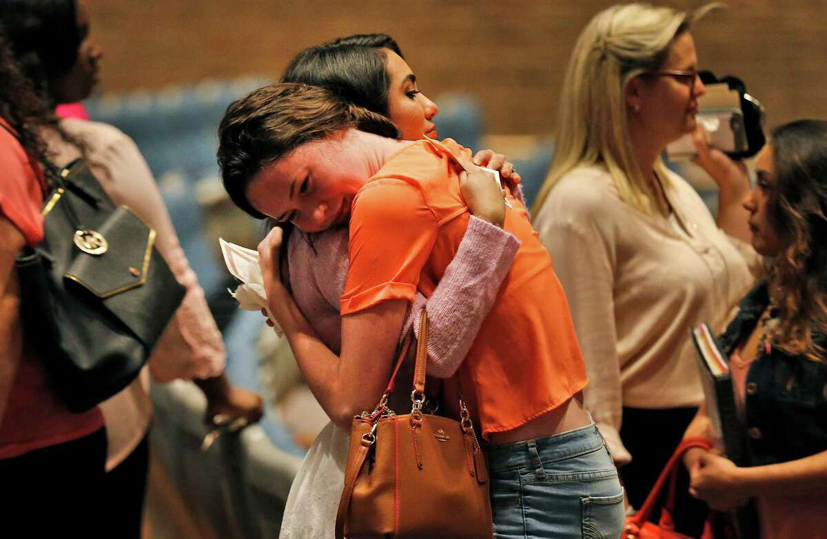 Two women embrace as friends and family attend a memorial service in honor of Emilee Diane Hurst at Judson High School's Performing Arts Center on Friday, Apr. 15, 2016. Pastors, teachers and friends spoke lovingly of Hurst who died on Monday of a gunshot wound from an ex-boyfriend. Hurst was a senior at Judson and participated in the school's dance team as well as the agriculture program. Many mourners wore pink - Hurst's favorite color - as they grieved in their loss. But the memorial also had moments of laughter as those close to Hurst recalled how she lived her life.