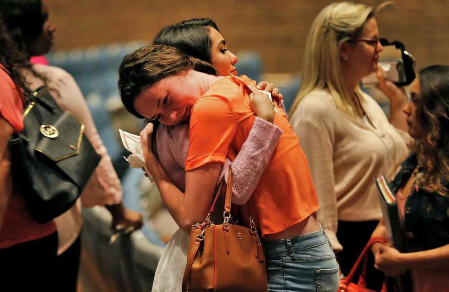 Two women embrace as friends and family attend a memorial service in honor of Emilee Diane Hurst at Judson High School's Performing Arts Center on Friday, Apr. 15, 2016. Pastors, teachers and friends spoke lovingly of Hurst who died on Monday of a gunshot wound from an ex-boyfriend. Hurst was a senior at Judson and participated in the school's dance team as well as the agriculture program. Many mourners wore pink - Hurst's favorite color - as they grieved in their loss. But the memorial also had moments of laughter as those close to Hurst recalled how she lived her life. Photo: Kin Man Hui, San Antonio Express-News / ©2016 San Antonio Express-News