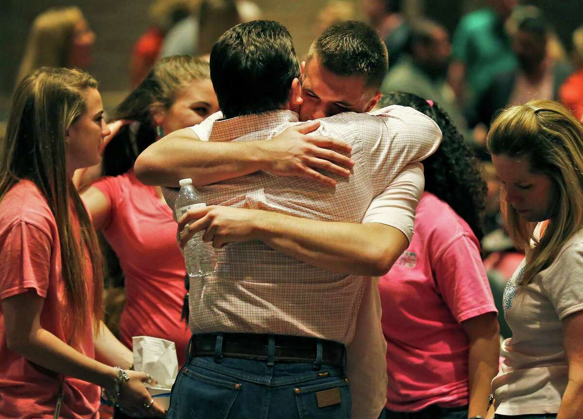 Brandon Walters, who identified himself as the boyfriend of Emilee Diane Hurst when he addressed the room, receives a hug after Hurst's memorial service at Judson High School's Performing Arts Center on Friday, Apr. 15, 2016. Pastors, teachers and friends spoke lovingly of Hurst who died on Monday of a gunshot wound from an ex-boyfriend. Hurst was a senior at Judson and participated in the school's dance team as well as the agriculture program. Many mourners wore pink - Hurst's favorite color - as they grieved in their loss. But the memorial also had moments of laughter as those close to Hurst recalled how she lived her life.