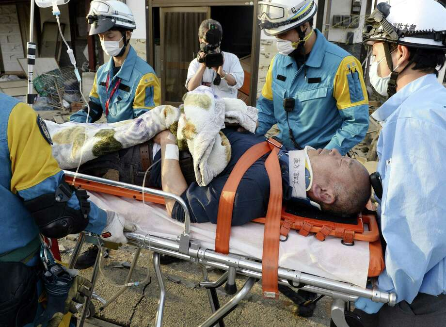 A man rescued from a collapsed  house is carried in Mashiki, Kumamoto prefecture, southern Japan Saturday, April 16, 2016. A powerful earthquake struck southern Japan early Saturday, barely 24 hours after a smaller quake hit the same region. (Ryosuke Uematsu/Kyodo News via AP) JAPAN OUT, MANDATORY CREDIT Photo: Ryosuke Uematsu, SUB / Associated Press / Kyodo News
