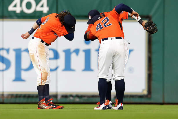 Houston Astros center fielder Carlos Gomez (30), Colby Rasmus, and George Springer celebrate the Astros win after an MLB baseball game at Minute Maid Park, Friday, April 15, 2016, in Houston.