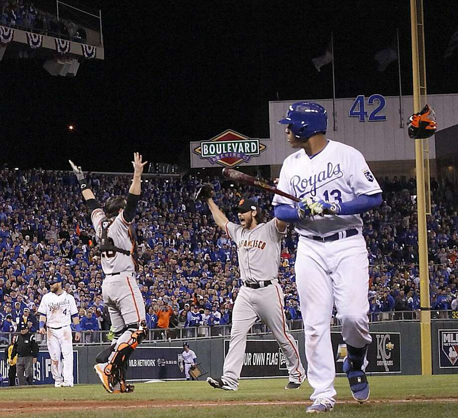 Buster Posey (left) and Madison Bumgarner celebrate the last out of the 2014 World Series, which stranded the tying run on third base in Game 7 and still hasn't been forgotten by the Royals. Photo: Carlos Avila Gonzalez, The Chronicle