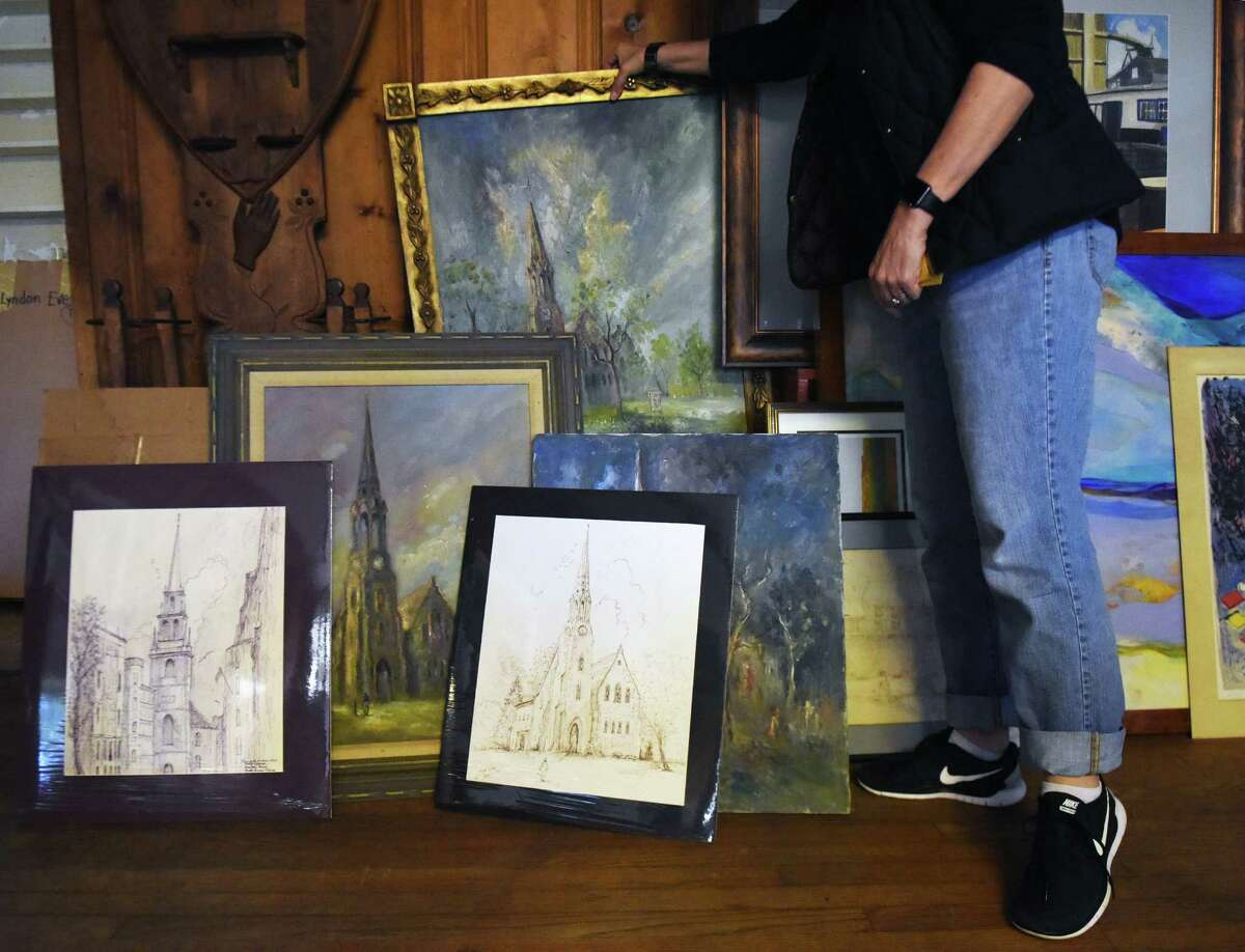 Amanda Jones organizes artwork of local Greenwich churches, a part of John and Gretchen Tatge's collection compiled over their decades living in Greenwich.