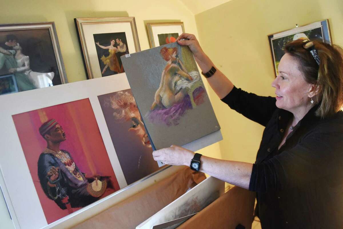 Amanda Jones shows a painting by her mother, Gretchen Tatge.