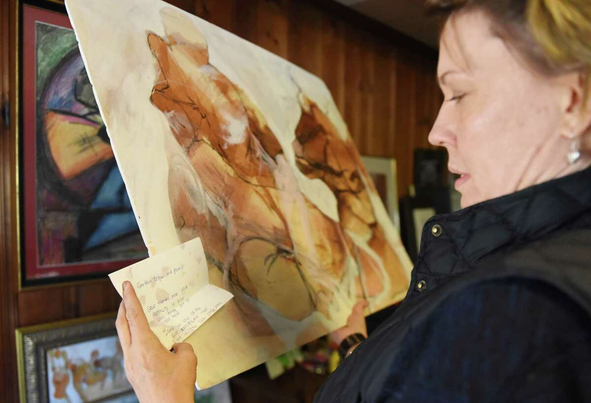Amanda Jones reads a letter accompanying a piece of art given to her parents, John and Gretchen Tatge, at the Tatges' former home in Greenwich on Thursday.