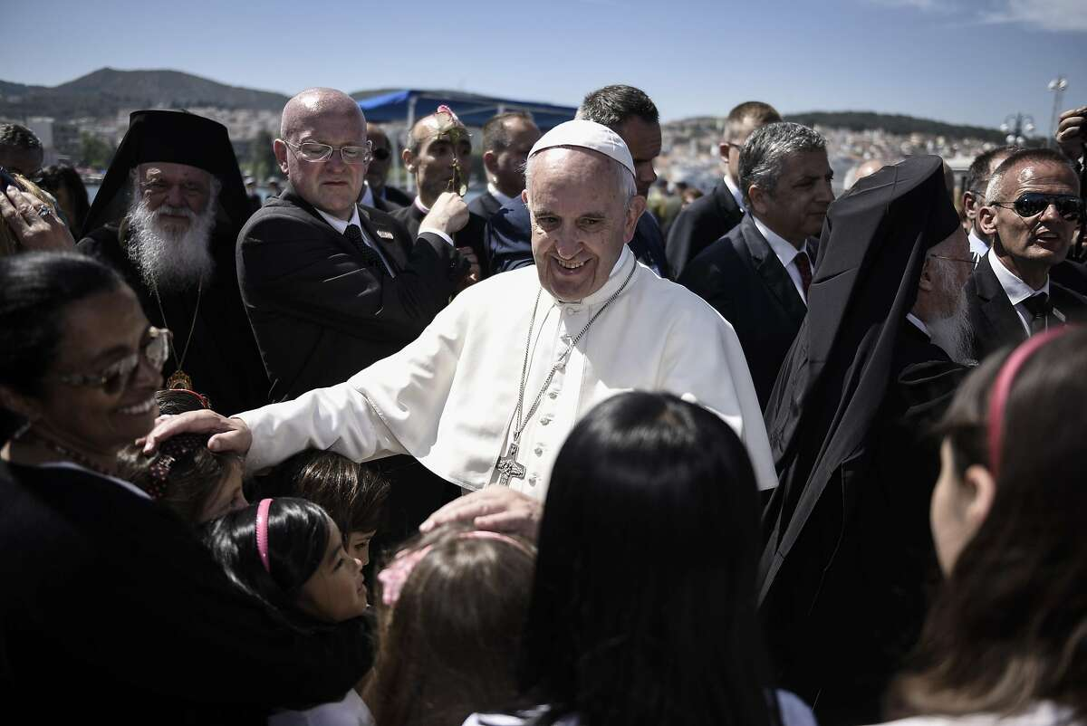 """In this photo released by Greek Prime Minister's office on Saturday, April 16, 2016, Pope Francis, greets children at the port of Mytilene, on the Greek island of Lesbos. Pope Francis implored Europe on Saturday to respond to the migrant crisis on its shores """"in a way that is worthy of our common humanity,"""" during an emotional and provocative trip to Greece. (Andrea Bonetti/Greek Prime Minister's Office via AP)"""