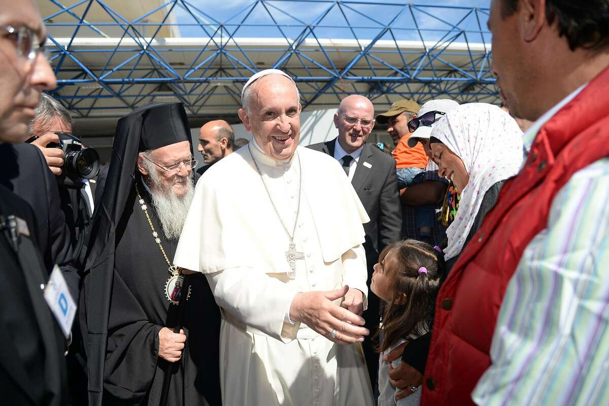 """TOPSHOT - Pope Francis (C) flanked by Archbishop of Constantinople and Ecumenical Patriarch Bartholomew I, greets a group of Syrian refugees that will fly back to the Vatican with him on April 16, 2016 at the airport of Mytilene, in the Greek island of Lesbos. Twelve Syrian refugees were accompanying Pope Francis on his return flight to Rome after his visit to Lesbos on Saturday and will be housed in the Vatican, the Holy See said. """"The pope has desired to make a gesture of welcome regarding refugees, accompanying on his plane to Rome three families of refugees from Syria, 12 people in all, including six children,"""" a Vatican statement said. AFP PHOTO POOL / FILIPPO MONTEFORTE / AFP PHOTO / POOL / FILIPPO MONTEFORTEFILIPPO MONTEFORTE/AFP/Getty Images"""