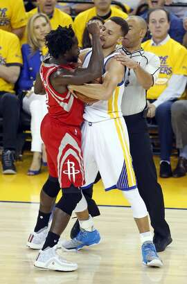 Golden State Warriors' Stephen Curry and Houston Rockets' Patrick Beverley tussle in 1st quarter in Game 1 of 1st round of NBA Playoffs at Oracle Arena in Oakland, Calif., on Saturday, April 16, 2016.