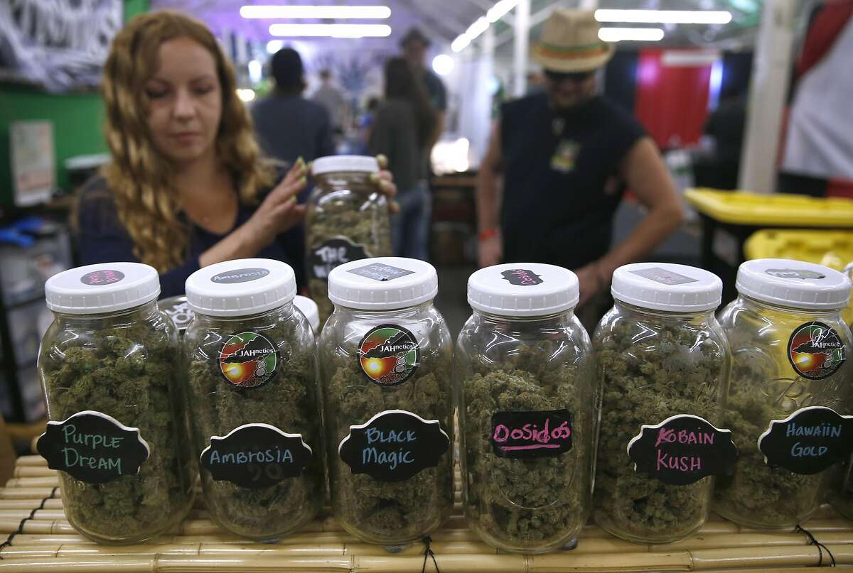 Brandy Turnbull sets up a display of medicinal marijuana for the Buddha's Pantry booth at the Hempcon Cannabis Festival at the Cow Palace in Daly City on Saturday, April 16, 2016.
