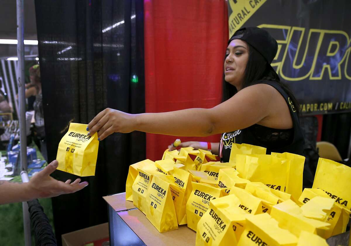 Paloma Alvarado hands out free samples of medicated popcorn to attendees of the Hempcon Cannabis Festival at the Cow Palace in Daly City on Saturday, April 16, 2016.