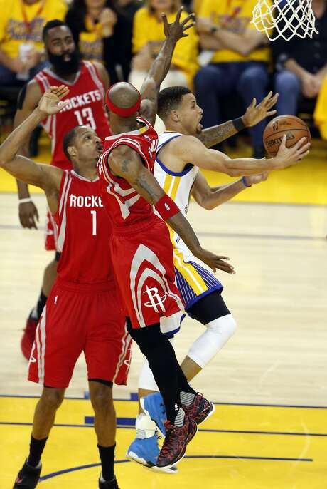 Golden State Warriors' Stephen Curry scores against Houston Rockets' Trevor Ariza (1) and Jason terry in 2nd quarter in Game 1 of 1st round of NBA Playoffs at Oracle Arena in Oakland, Calif., on Saturday, April 16, 2016. Photo: Scott Strazzante, The Chronicle