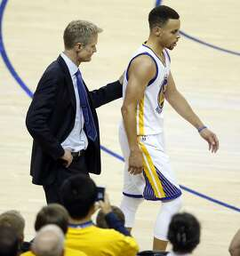 Golden State Warriors' head coach Steve Kerr pats Stephen Curry as Curry exits game in 2nd quarter against Houston Rockets in Game 1 of 1st round of NBA Playoffs at Oracle Arena in Oakland, Calif., on Saturday, April 16, 2016.