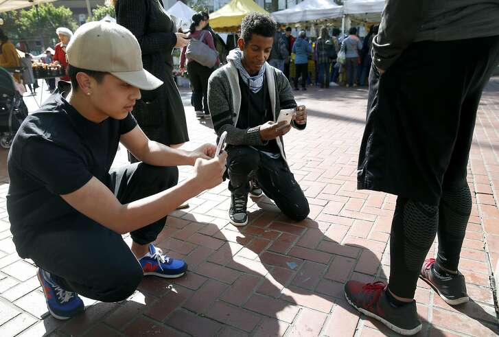 Rigo Concillion and Elishes Cavness photograph shoes while on the lookout for fashion trends at the UN Plaza Farmers Market for a class run by Mikel Rosen at the Art Institute of California in San Francisco, Calif. on Wednesday, April 13, 2016.
