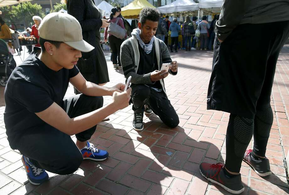 Rigo Concillion (left) and Elishes Cavness photograph shoes at the U.N. Plaza farmers' market in S.F. for a trend-forecasting class at the Art Institute of California-San Francisco taught by Mikel Rosen. Photo: Paul Chinn, The Chronicle