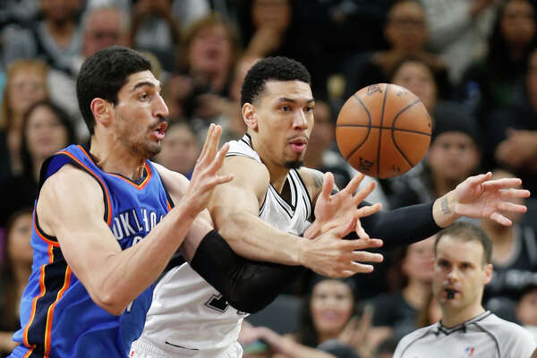 SAN ANTONIO,TX - APRIL 12: Danny Green #14 of the San Antonio Spurs battles Enes Kanter #11 of the Oklahoma City Thunder for a loose ball at AT&T Center on April 12, 2016 in San Antonio, Texas.  NOTE TO USER: User expressly acknowledges and agrees that , by downloading and or using this photograph, User is consenting to the terms and conditions of the Getty Images License Agreement. (Photo by Ronald Cortes/Getty Images)