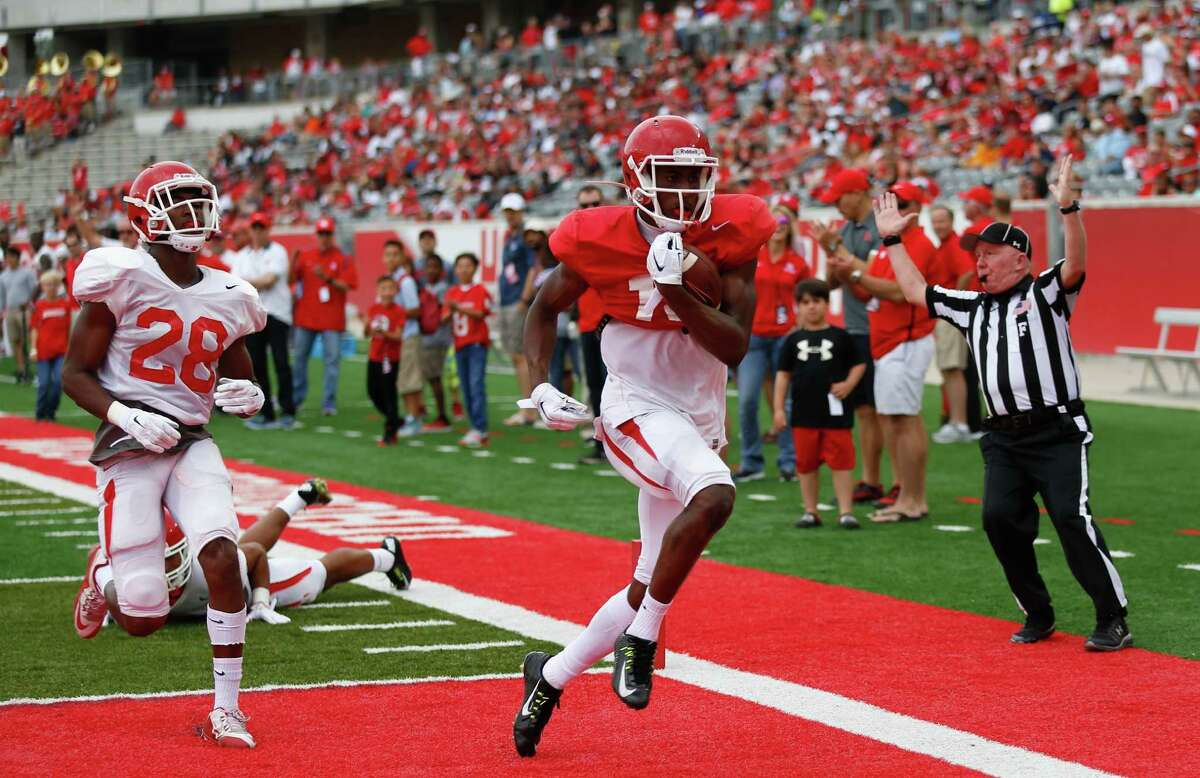 Houston Cougars wide receiver Isaiah Johnson (14) scores on as safety Darius Gilbert (28) is unable to stop him during the Houston Cougars Red and White game, Saturday, April 16, 2016, in Houston.