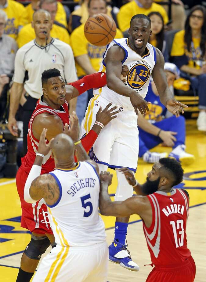 The Warriors' Draymond Green passes to Marreese Speights as the Rockets' Dwight Howard (left) and James Harden play defense in the playoff opener at Oracle Arena. Photo: Scott Strazzante, The Chronicle