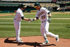 OAKLAND, CA - APRIL 16: Josh Reddick #22 of the Oakland Athletics celebrates a three-run homer with Stephen Vogt #21 of the Oakland Athletics in the first inning against the Kansas City Royals at O.co Coliseum on April 16, 2016 in Oakland, California.  (Photo by Lachlan Cunningham/Getty Images)