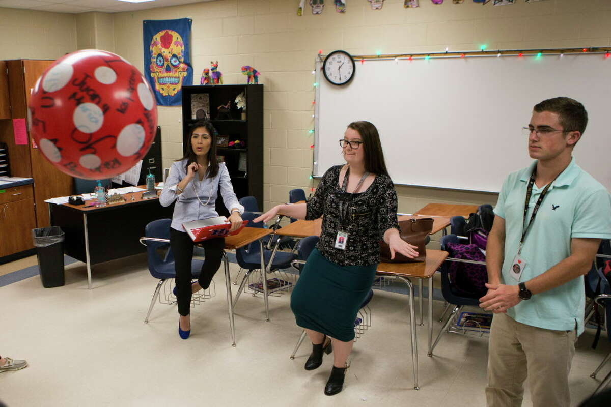 Hardin Jefferson High School Spanish language teacher Ana Rocha, second from the left, 26, interacts with her students, Breanna Kelley, center, 16, and during a language exercise on which the student who gets stuck with the ball after the music stops has to a create conditional sentence from the verb provided by the teacher. Since Rocha qualified for President Barak Obama's temporary work permit known as deferred action for childhood arrivals, Rocha has health insurance, contributes to Social Security and began to drive.