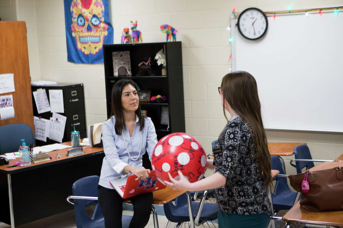 Hardin Jefferson High School Spanish language teacher Ana Rocha, left, 26, interacts with her student Breanna Kelley, right, 16, during a language exercise on which the student who gets stuck with the ball after the music stops has to a create conditional sentence from the verb provided by the teacher. Since Rocha qualified for President Barak Obama's temporary work permit known as deferred action for childhood arrivals, Rocha has health insurance, contributes to Social Security and began to drive.
