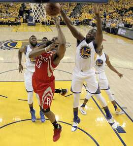 Draymond Green (23) defends against a shot by James Harden (13) in the first half as the the Golden State Warriors played the Houston Rockets in the first round of the Western Conference Playoffs at Oracle Arena in Oakland, Calif., on Saturday, April 16, 2016.