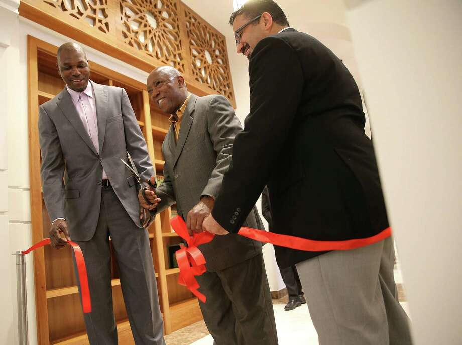 Hakeem Olajuwon, Mayor Sylvester Turner and Executive Director Ameer Abuhalimeh cut the ribbon for the Library of Islamic Knowledge on Saturday. Photo: Elizabeth Conley, Staff / © 2016 Houston Chronicle