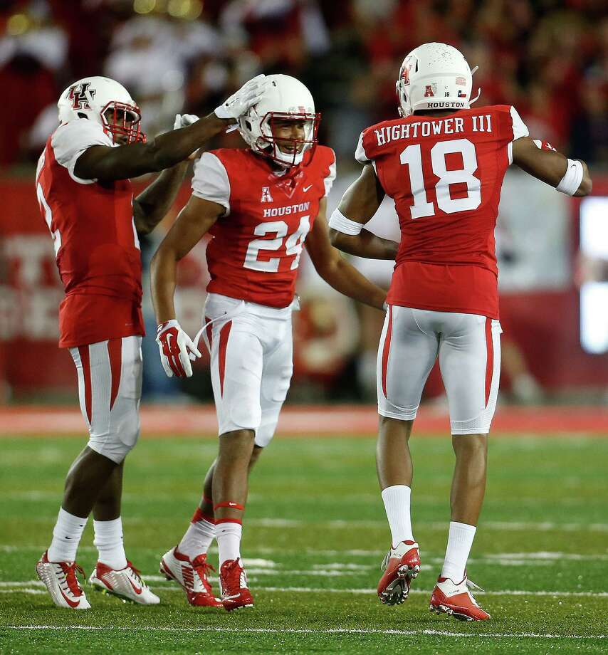 Houston Cougars safety Khalil Williams (2) celebrates with cornerback Jeremy Winchester (24) and cornerback Lee Hightower (18) after stopping the final Cincinnati Bearcats drive during the second half of a college football game at TDECU Stadium on Saturday, Nov. 7, 2015. Photo: Karen Warren, Houston Chronicle / © 2015 Houston Chronicle