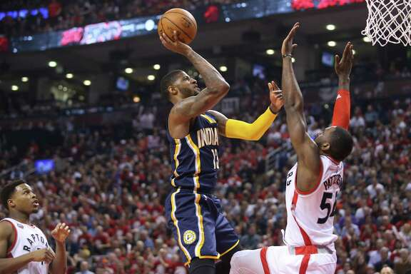 TORONTO, CANADA - APRIL 16: Paul George #13 of the Indiana Pacers shoots against Patrick Patterson #54 of the Toronto Raptors in Game One of the Eastern Conference Quarterfinals during the 2016 NBA Playoffs on April 16, 2016 at the Air Canada Centre in Toronto, Ontario, Canada. NOTE TO USER: User expressly acknowledges and agrees that, by downloading and/or using this photograph, user is consenting to the terms and conditions of the Getty Images License Agreement. Mandatory copyright notice. (Photo by Tom Szczerbowski/Getty Images)
